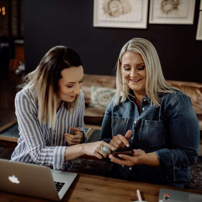 Image of SocialUs founders Jess and Meagan conducting a social media health check on a mobile phone.