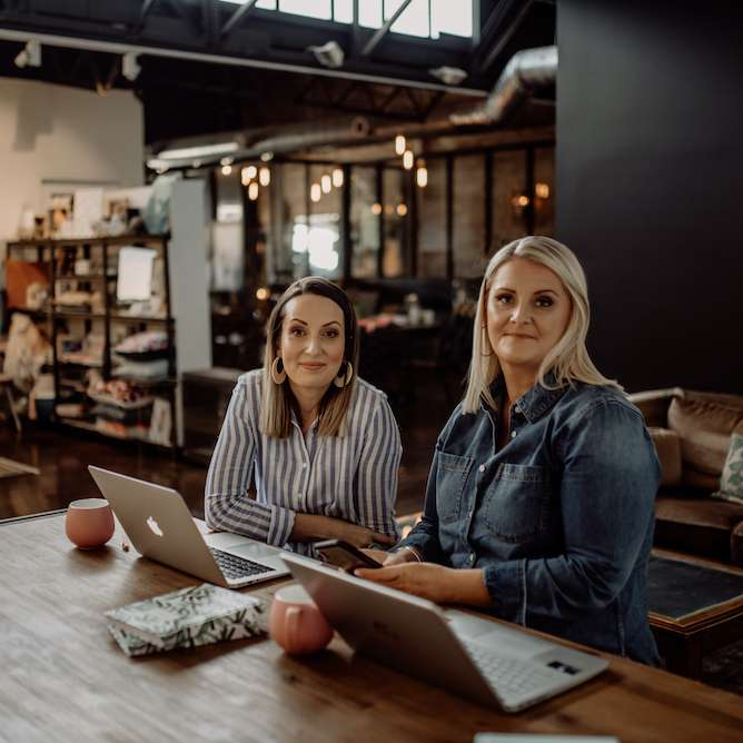 Image of SocialUs founders Jess and Meagan siting at a table in a cafe on their laptops.