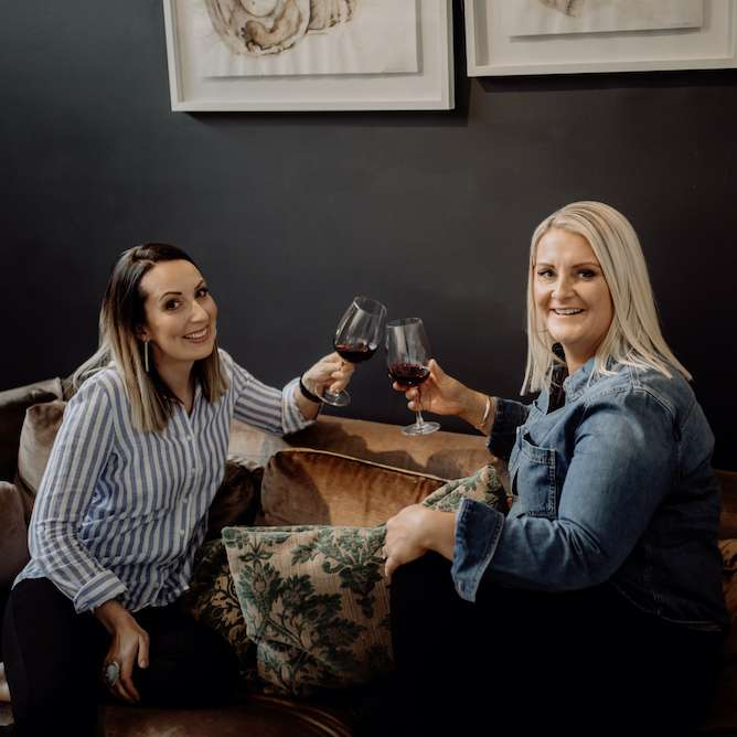 Image of SocialUs founders Jess and Meagan clinking wine glasses filled with red wine.